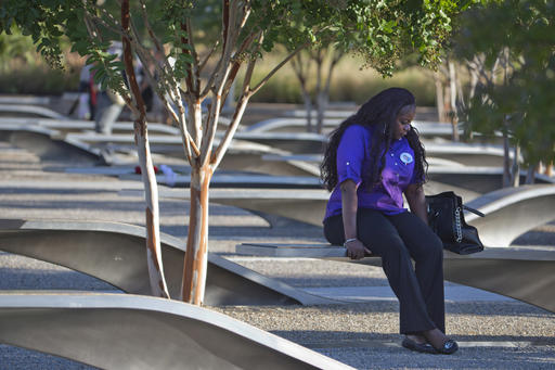 FILE- In this Sept. 11, 2015 file photo, a woman wearing a pin in remembrance of Johnnie Doctor, Jr., visits the Pentagon Memorial on the 14th anniversary of the September 11th attacks. Victims' relatives and dignitaries will convene Sunday, Sept. 11, 2016, at the memorial for one of the constants in how America remembers 9/11 after 15 years, the anniversary ceremony itself. (AP Photo/Jacquelyn Martin, File)