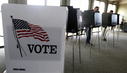 FILE - In this March 18, 2014 file photo, voters cast their ballots in the Illinois primary in Hinsdale, Ill. Republicans have gained ground on Democrats' strength in registering voters in three battleground states _ and kept their razor-thin advantage in Iowa, offering some hope for Donald Trump and raising the stakes over ballot access in the final weeks before Election Day. (AP Photo/M. Spencer Green, File)