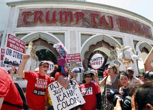 FILE - In this Wednesday, July 6, 2016, file photo, striking workers shout and hold signs as they picket outside the Trump Taj Mahal hotel and casino in Atlantic City, N.J. On Monday, Oct. 10, 2016, the last vestige of Donald Trump will vanish from Atlantic City when the Trump Taj Mahal casino shuts down. Trump, the Republican presidential nominee, tells The Associated Press that he's sad that the Taj Mahal's new owner, his friend and fellow billionaire Carl Icahn, and the casino workers' union couldn't reach a deal to keep the casino open. (AP Photo/Mel Evans, File)