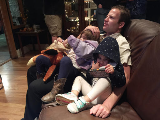 Elliot Fladen of Denver, Colo., watches the presidential debate with his daughters Dagny, 5, and Areli, 2. Parents watching the prime time presidential debate with their children Sunday, Oct. 9, 2016, faced a dilemma: Let their kids witness political history, or send them to bed early to avoid awkward conversations? When CNN's Anderson Cooper asked GOP nominee Donald Trump about his 2005 vulgar comments about women, Fladen quickly checked to make sure Dagny's earbuds were in. (AP Photo/Kristen Wyatt)