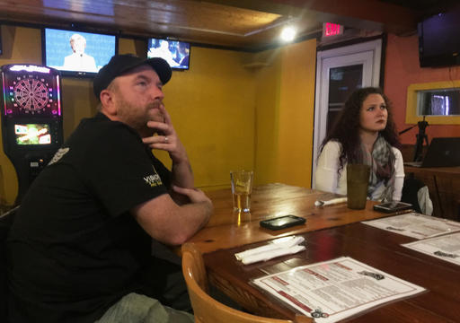 Undecided voters Damon Holter, left, and Kyia Britts watch the third and final presidential debate between Democrat Hillary Clinton and Republican Donald Trump at Bo's 'N Mine bar and grill in River Falls, Wis., Wednesday, Oct. 19, 2016. (AP Photo/Jeff Baenen)