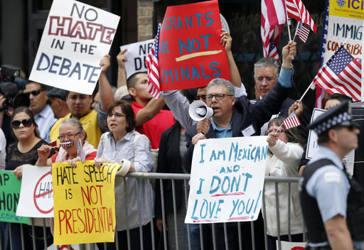 FILE - In this June 29, 2015, file photo, protesters gather across the street from a restaurant in Chicago before Republican presidential candidate Donald Trump spoke to members of the City Club of Chicago. When it comes to connecting with and motivating Hispanic voters, GOP candidates across the country face an exceptional obstacle: their own presidential nominee. Trump's harsh words about immigrants in the country illegally and his vows to deport them and build a border wall have turned off many of the estimated 27 million Latinos eligible to vote. (AP Photo/Charles Rex Arbogast, File)