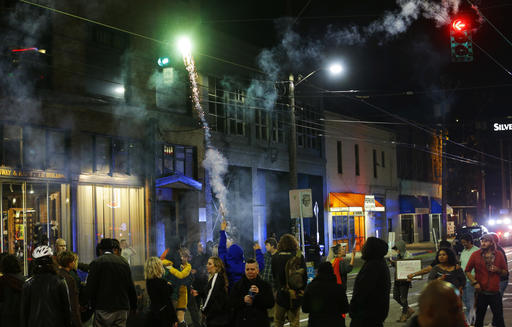 A protester sets off fireworks during a protest against President-elect Donald Trump, Wednesday, Nov. 9, 2016, in Seattle's Capitol Hill neighborhood. (AP Photo/Ted S. Warren)
