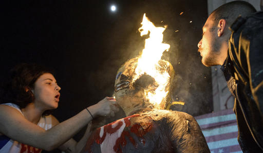 """FILE - In this Wednesday, Nov. 9, 2016 file photo, a woman who identified herself as J. Stroh sets fire to an effigy of Donald Trump, as a man who identified himself as Blue Velvet blows on the flames, during an anti-Trump protest at Lee Circle in New Orleans. Jim Mullen, president of Allegheny College in Meadville, Pa., which awards a prize each year for civility in public life says, """"We can all point to incidents in campaigns across history, but I think this one probably does represent a new place in terms of incivility."""" (Matthew Hinton/The Advocate via AP)"""