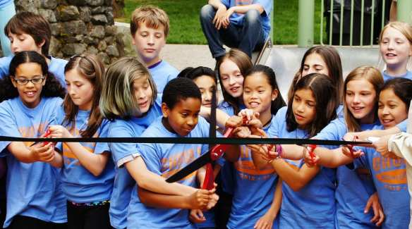 Kids from Stevens Elementary School cut the ribbon with a comically large pair of scissors, and several small pairs of scissors.
