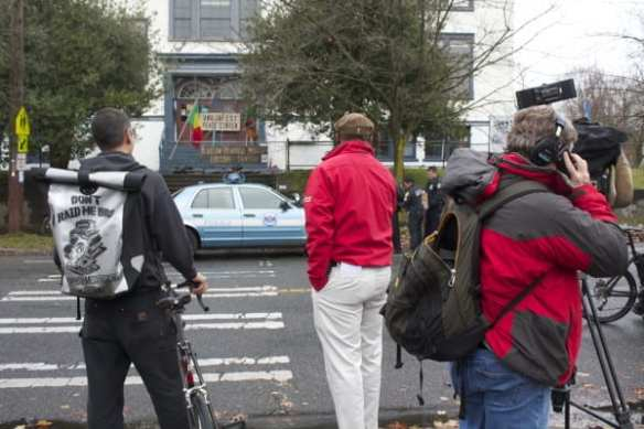 Media and a protester watch the fourth arrest