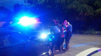 The suspect is taken into custody Sunday night as an officer examines the shoulder the suspect said was bitten (Image: Jacob Olson)