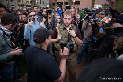 An open-carry gun advocate is confronted by protesters