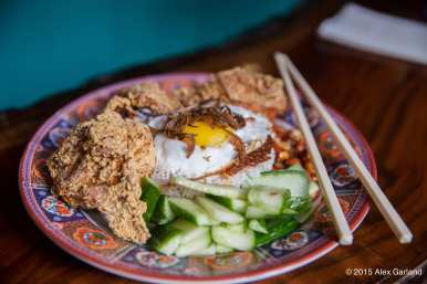 "Nasi lemak ayam goren belacan -- ""coconut-pandan rice, sambal belecan, crispy anchovies, peanuts, cucumbers, fried cicken with belecan (shrimp paste), choice of fried or boiled egg"""