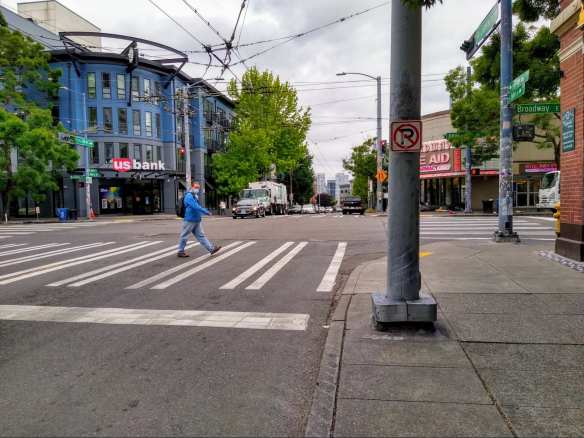 A person crossing the street in the north-south crosswalk at Broadway and John