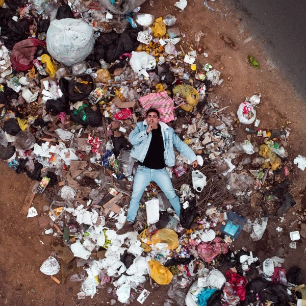 man lying in plastic rubbish