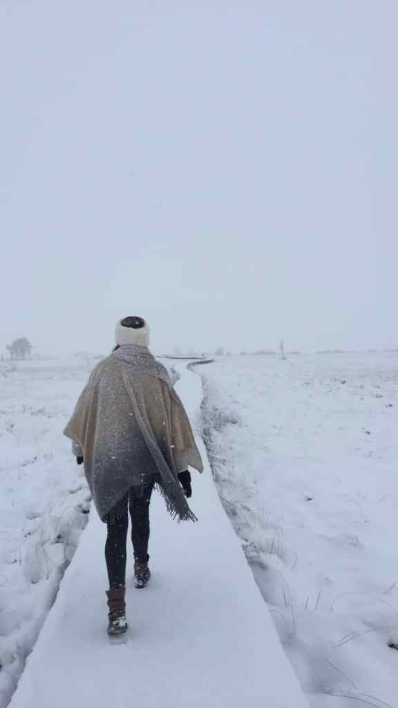 Girl with a hair band walking on a long snowy path