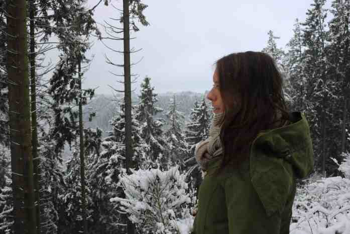 Side portrait of a girl with a kaki coat in a snowy landscape with pines