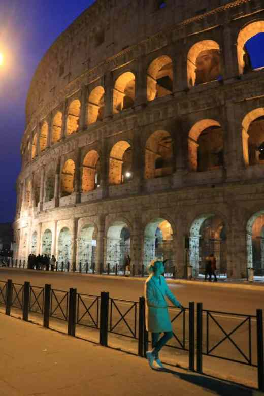 Tiny blond girl looking up at the huge Colosseum at night