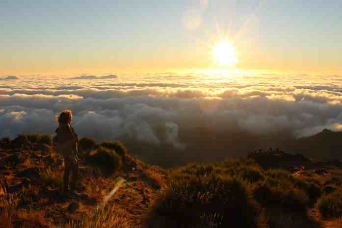 Girl on the top of a mountain watching the sunrise and overlooking the clouds