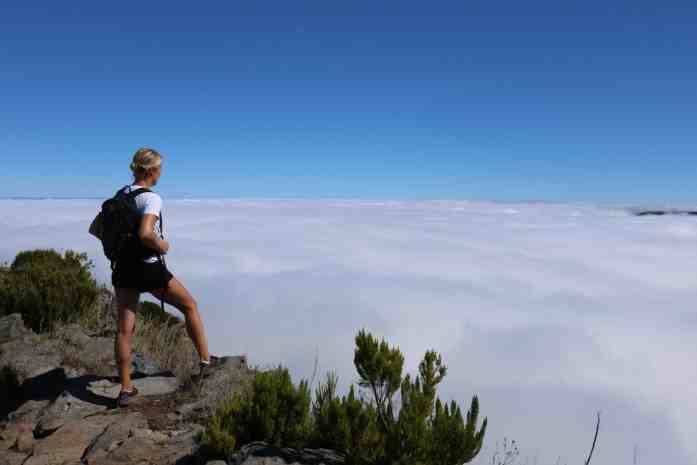 Girl with a backpack on looking over the clouds