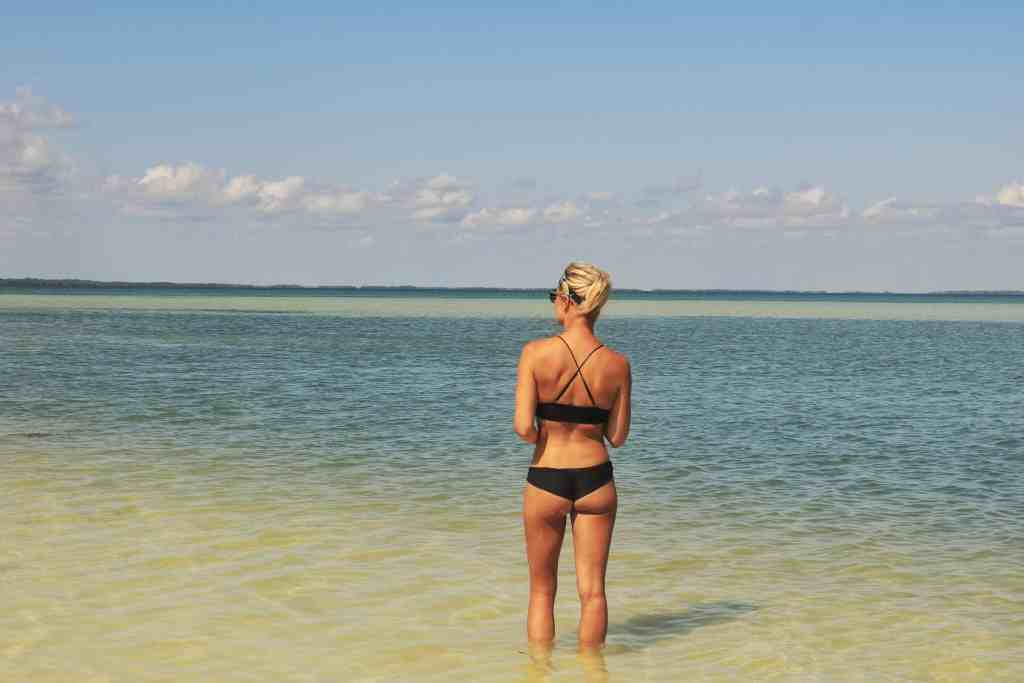 Back view of a girl standing in the ocean that has different shades of blue