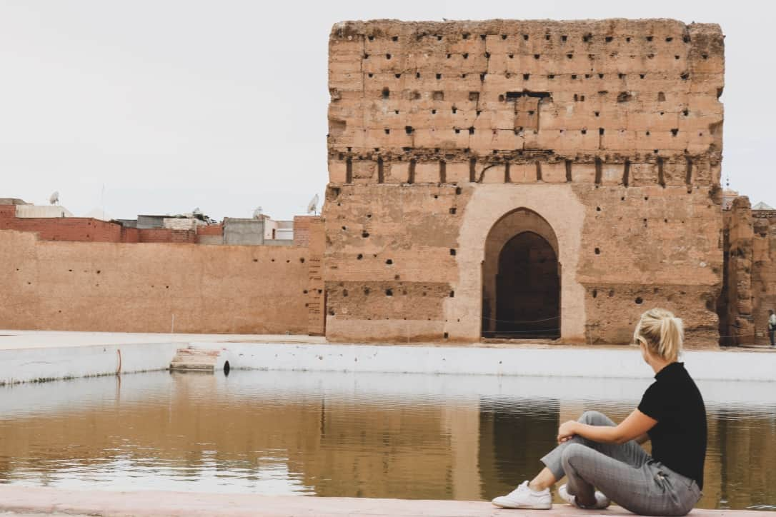 Girl sitting in front of the gate of El Badi Palace in Marrakech