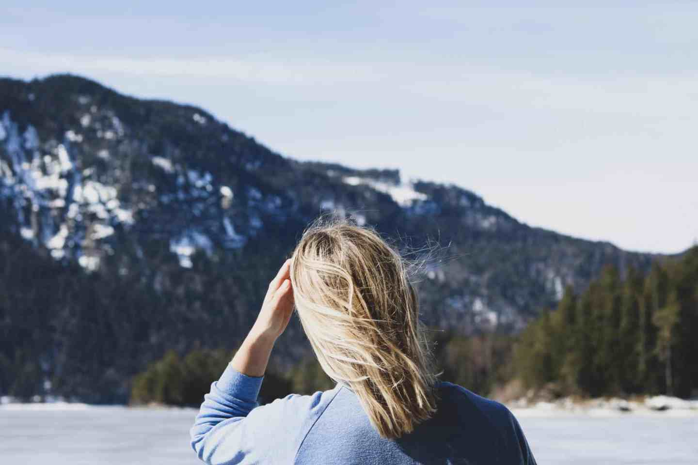 Girl with blonde hair standing in front of a snowy mountain with pine trees