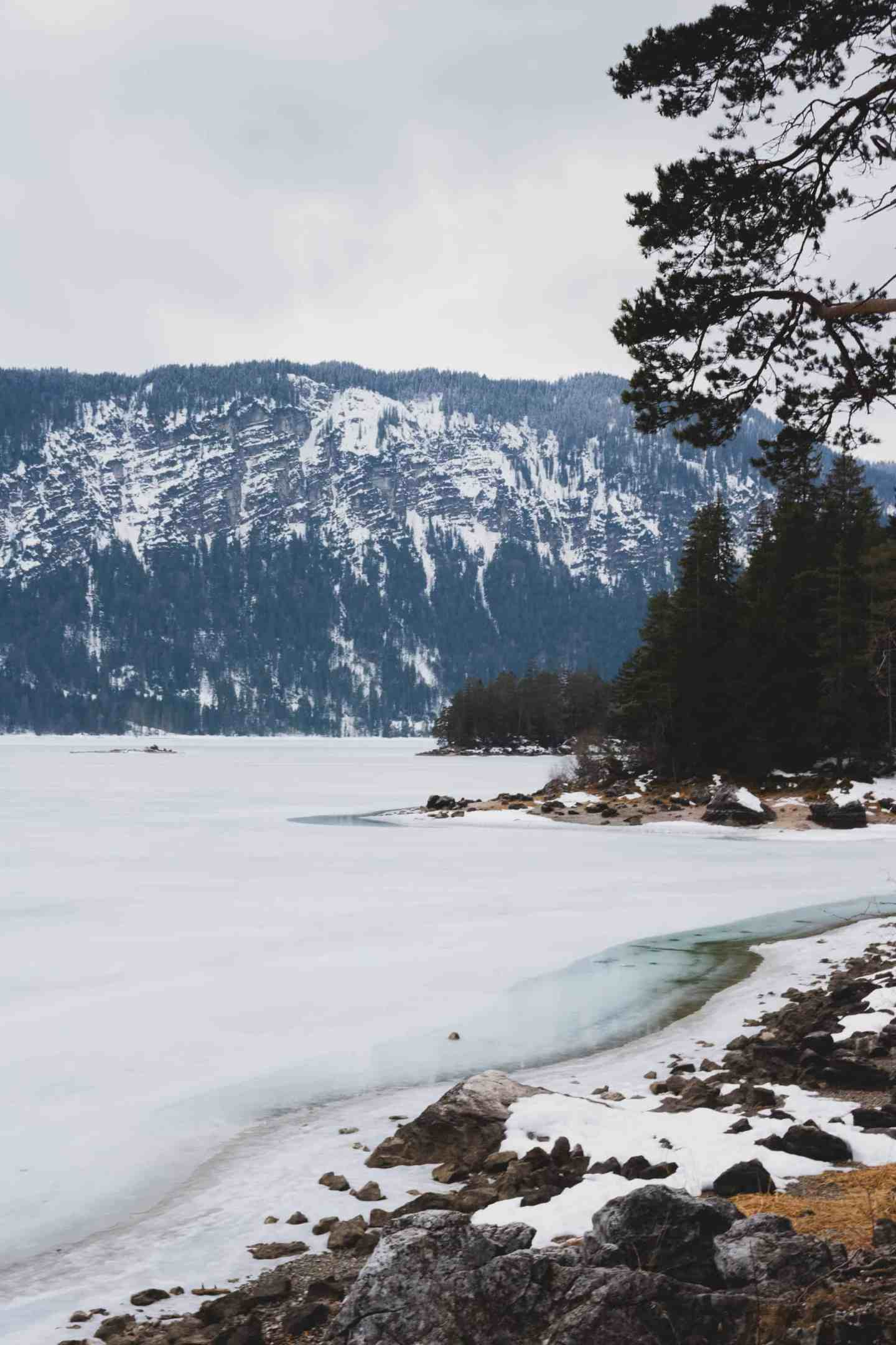 Frozen lake, a snowy mountain and pine trees