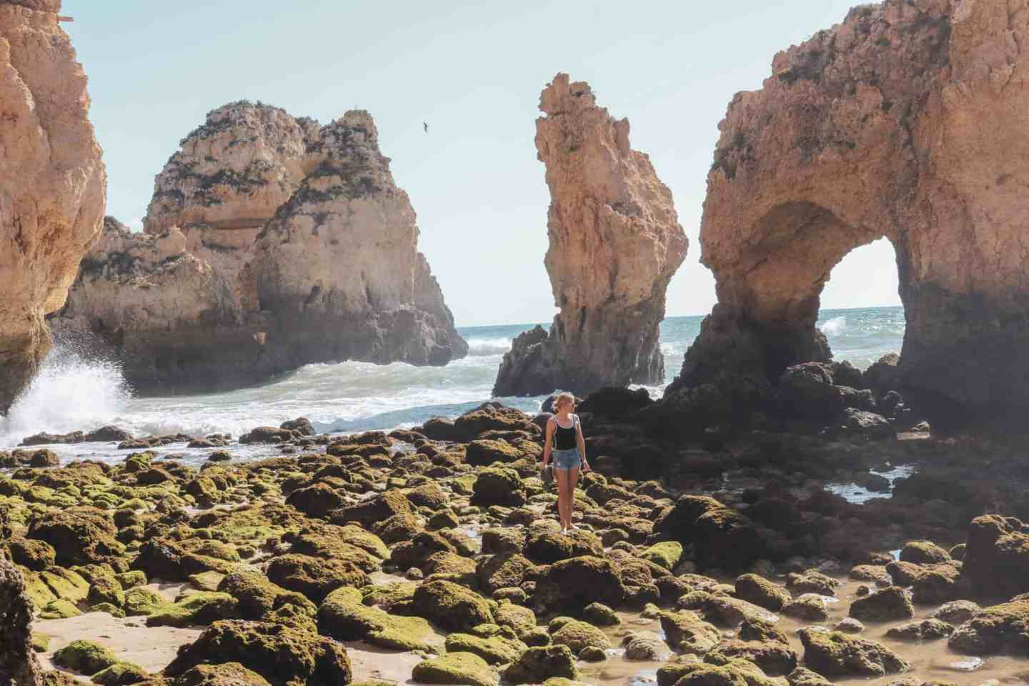 Girl standing on a few rocks and the ocean in Algarve