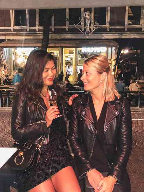 Two girls with leather jackets sitting in de witte de withstraat in Rotterdam