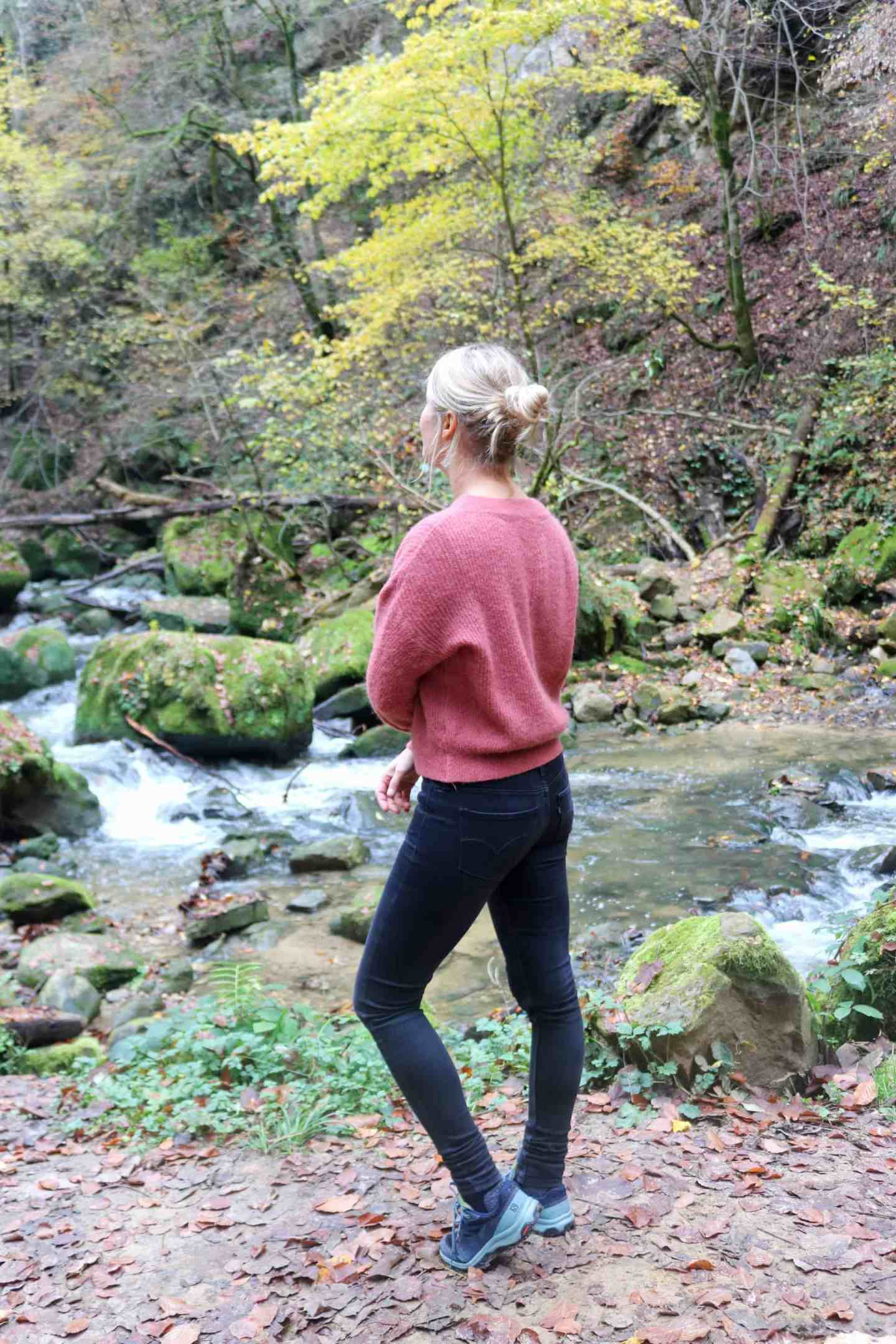 Girl in front of a river hiking müllerthal trail