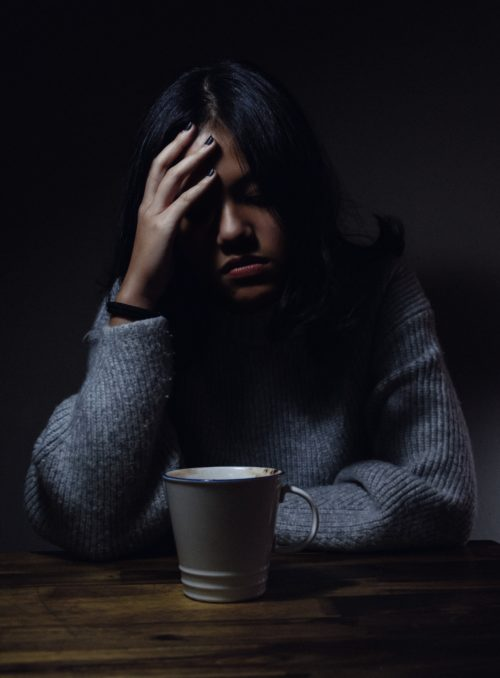 Woman in gray sweater in dark room