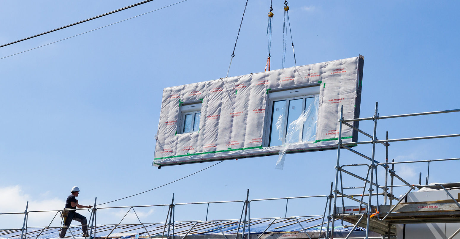 hight resolution of an offsite manufactured wall panel is lowered onto an energiesprong house in longueau france during a retrofit credit energiesprong international