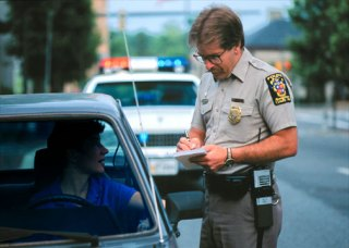 Highway patrol officer collecting information about the driver of a car he has pulled over. The driver is a young man in a blue shirt.