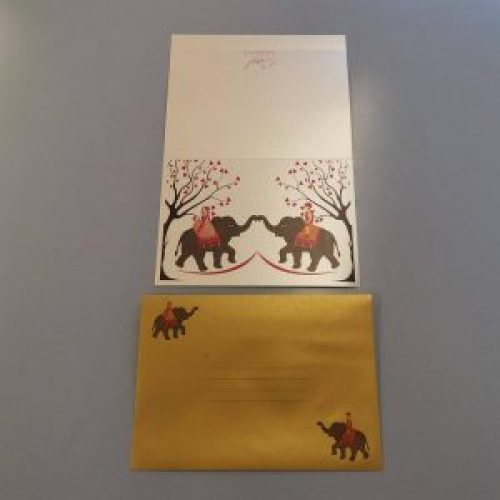 A5 landscape orientation invitation card with an Indian couple on elephants - outside view. A matching metallic gold envelope with the same couple and elephants design.