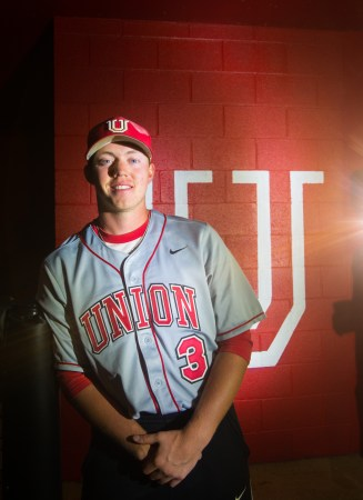 Trae Bain, junior exercise major, poses for a portrait by the dugout. | Photo by Victor Miller.