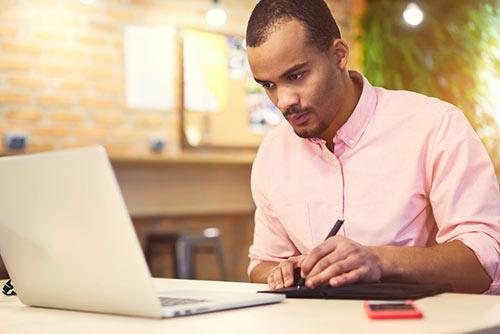 man at laptop taking notes