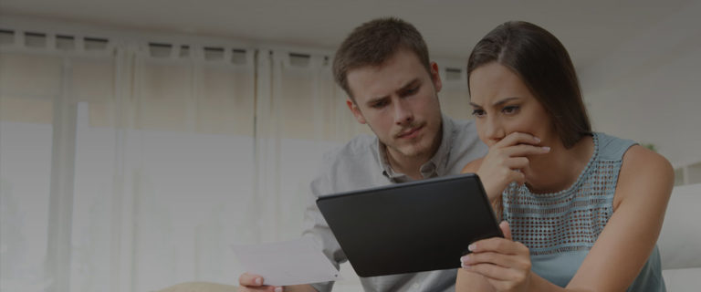 confused couple reading tablet