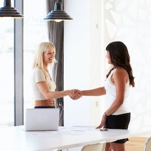 Gain a qualification - Two Young Professional Women in office shaking hands