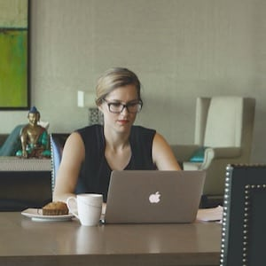 The Career Academy Stay Motivated - Young Professional Woman sitting at desk with muffin and coffee working on laptop