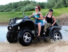 two woman riding an ATV