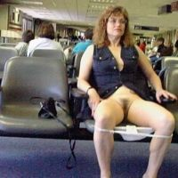 Mature lady in a short dress showing her bottomless pussy