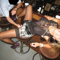 In a short skirt inside a bar and getting her pussy fondled