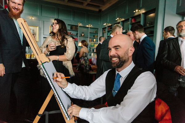 Top Irish Caricature Artist Allan Cavanagh at work drawing guests at a wedding reception