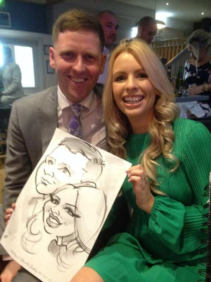 Couple laughing with their caricature by Allan Cavanagh