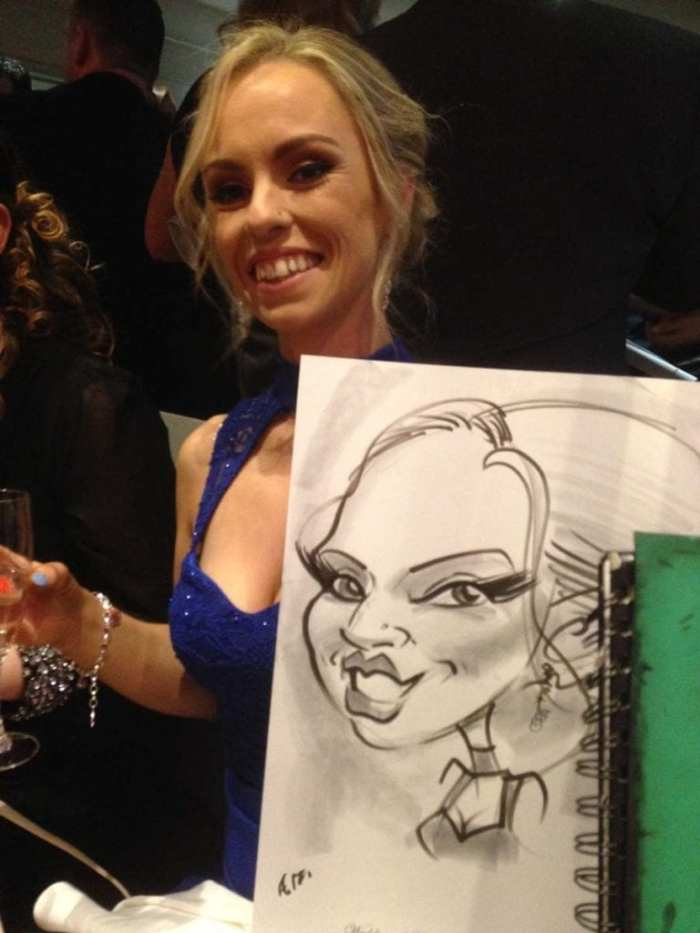 Woman holding caricature by artist Allan Cavanagh