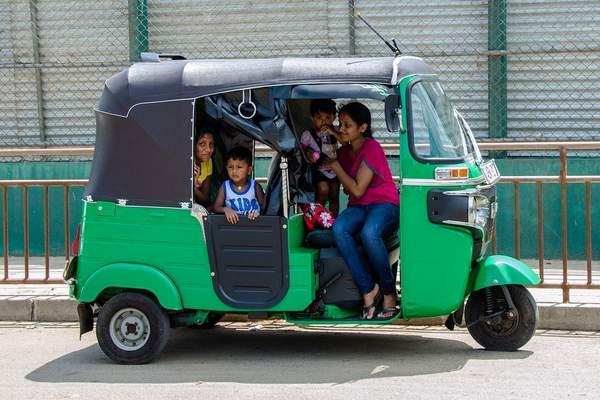 Image d'un tuk tuk indien avec une famille dedans pour illustrer l'article sur l'achat de voitures destinées aux familles nombreuses.