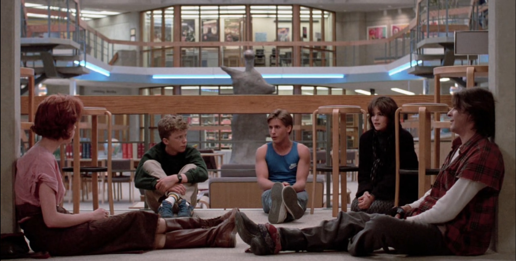 Molly Ringwald, Anthony Michael Hall, Emilio Estevez, Ally Sheedy, and Judd Nelson in The Breakfast Club (1985). Claire, Brian, Andrew, Allison, an awkward punk girl with dark hair falling over her face, wearing all black, and Bender, a boy with long brown hair wearing a red plaid shirt with cutoff sleeves and baggy khaki pants, are all sitting on the floor of the school library during detention, having a sober conversation.