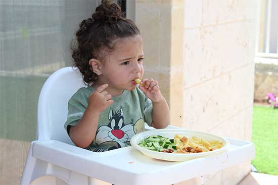 kid eathing nutritious food and not happy about it
