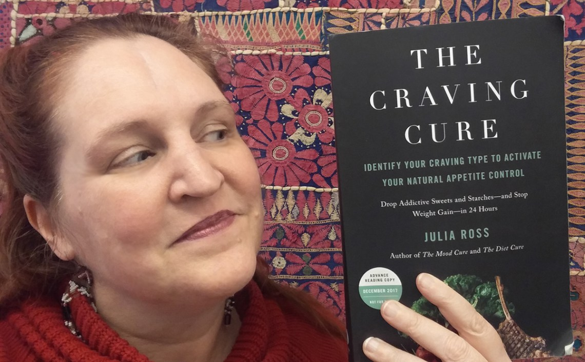 Carma holding a copy of The Craving Cure by Julia Ross