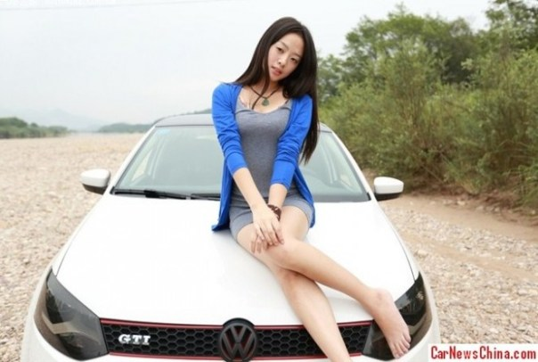 Pretty Chinese Girl hangs around and over the famously fake China-made Volkswagen Polo GTI