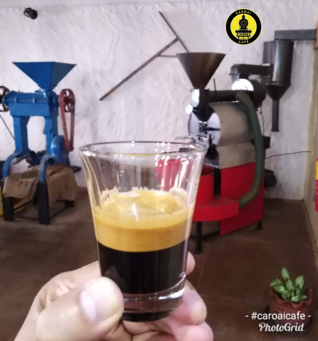 Un espresso con café de origen. Al fondo la trilladora y la tostadora de Caroai Café