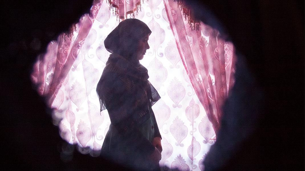 Afghanische Frau mit Kopftuch vor einem Vorhang