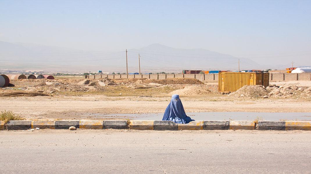 Afghanische Frau mit Burka sitzt am Strassenrand